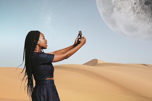 Donna di colore che scatta una foto in un deserto