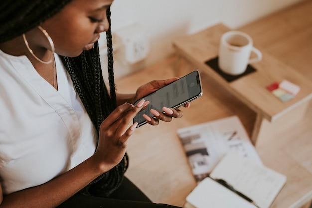 Donna di colore che scrive sul suo telefono