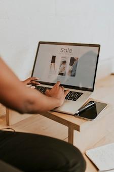 Donna di colore che usa un laptop su un tavolo di legno wooden