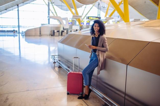 Donna di colore che aspetta il suo volo facendo uso del telefono cellulare all'aeroporto