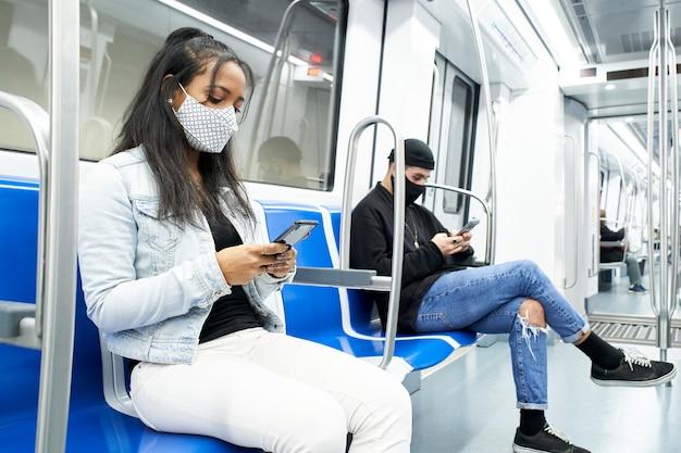 Una donna nera e un uomo bianco con maschere seduti nel vagone della metropolitana utilizzando lo smartphone
