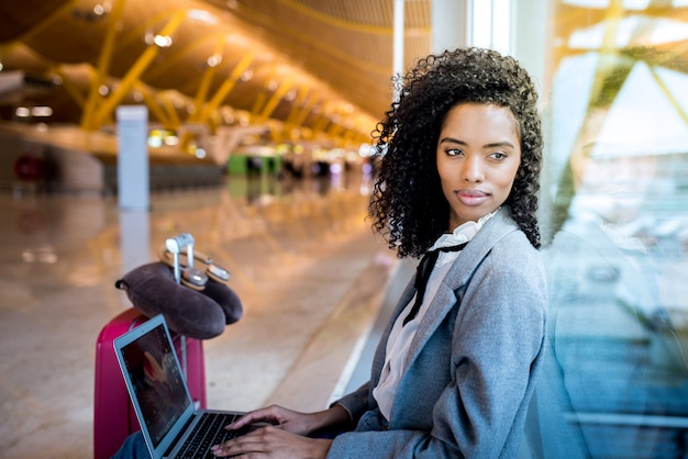 Donna di colore che lavora con il computer portatile all'aeroporto che aspetta alla finestra