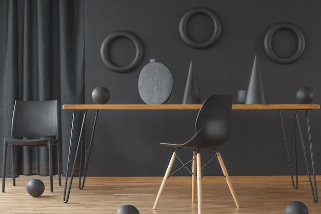 Interno della sala da pranzo nero e legno con tavolo a forcina, due sedie e sculture fatte a mano