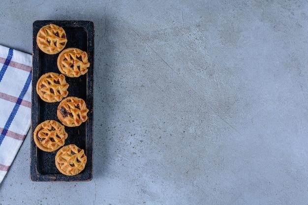 Una tavola di legno nera di biscotti alla frutta rotondi su uno sfondo di pietra.