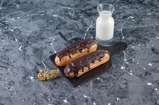 Un tagliere di legno nero di due gustosi bignè al cioccolato con una brocca di vetro di latte.