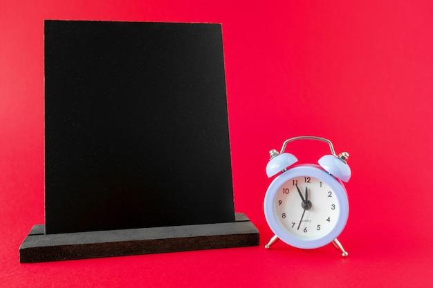 Lavagna in legno nero e sveglia su sfondo rosso con spazio copia