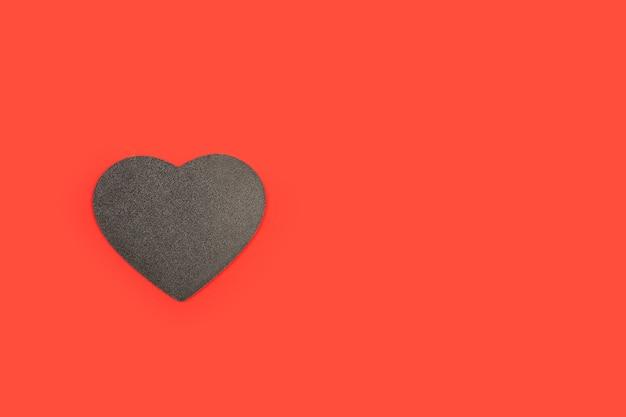 Un cuore di legno nero con copia spazio su uno sfondo rosso