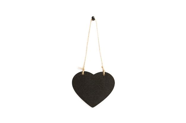 Un cuore in legno nero con copia spazio su uno sfondo bianco