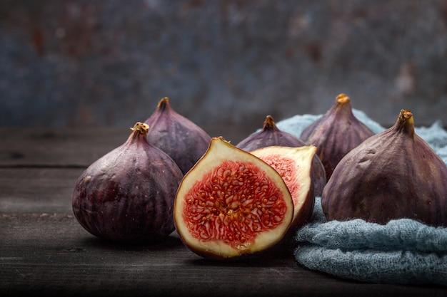 Su un tavolo di legno nero ci sono i frutti di fichi freschi. la bella frutta blu del fico si chiuda