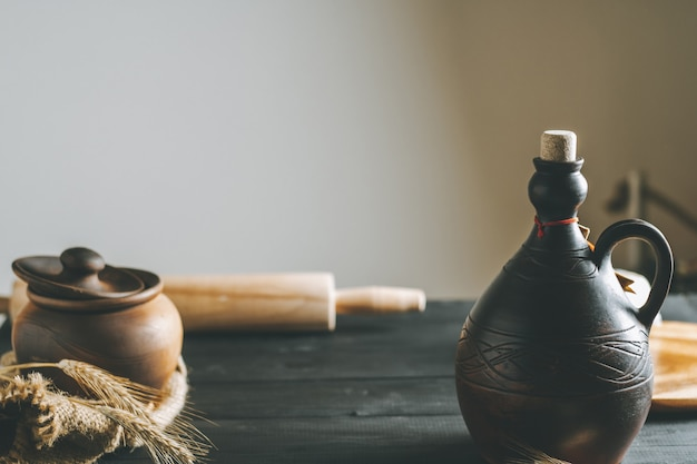 Tavolo in legno nero con mattarello, tela da imballaggio, spighette, vaso di argilla e bottiglia di olio alla luce del sole, spazio di copia