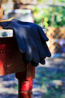 I guanti da lavoro neri giacciono su un vecchio tavolo di legno