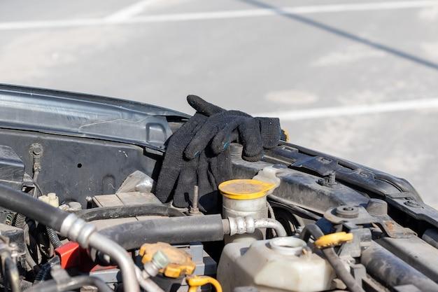 Guanti da lavoro neri di un meccanico sul bordo sotto un cofano aperto di un vano motore di un'auto flat-four (boxer)