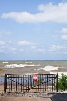 Il cancello in ferro battuto nero è chiuso ma mostra onde schiumose bianche e un cielo nuvoloso blu