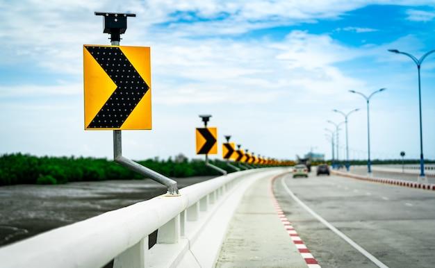Freccia nera e gialla sul segnale stradale della curva sul ponte con il pannello a celle solari