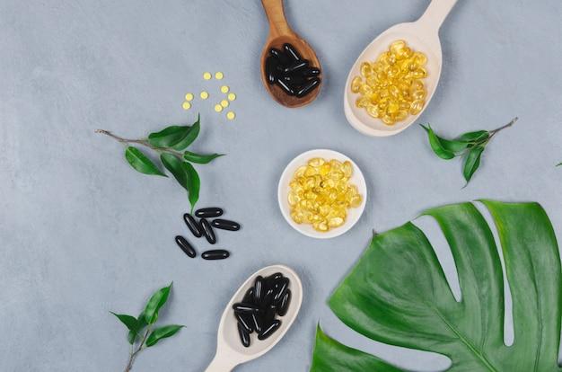 Pillole nere e gialle e cucchiai di legno