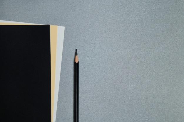 Fogli di carta neri, gialli e bianchi e una matita nera su sfondo grigio. lay piatto, copia spazio, vista dall'alto