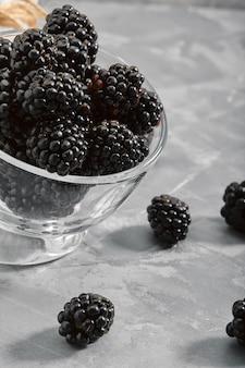 Blackberry su uno sfondo nero, primo piano, bacca fresca in una zucca su uno sfondo di cemento. copie dello spazio.