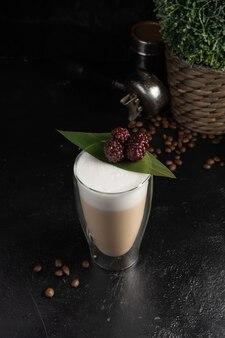 Blackberry latte in una tazza termica trasparente a due strati.