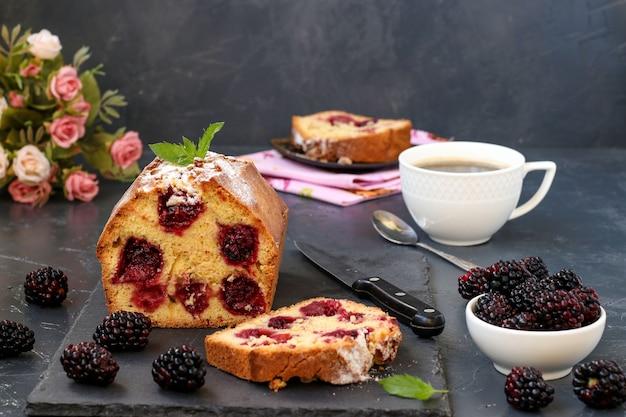 Un muffin alle more si trova su una tavola di ardesia su uno scuro