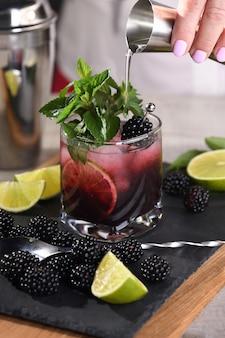 Cocktail di mojito estivo alla mora. bevanda alcolica biologica rinfrescante fredda con frutti di bosco, lime, menta