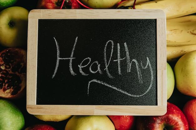 Lavagna sopra un mazzo di frutta con scritto sano
