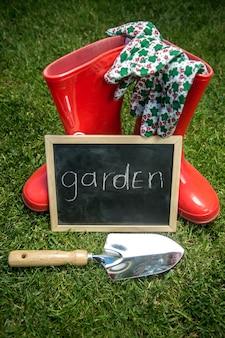 Lavagna sull'erba verde fresca accanto agli attrezzi da giardino con testo