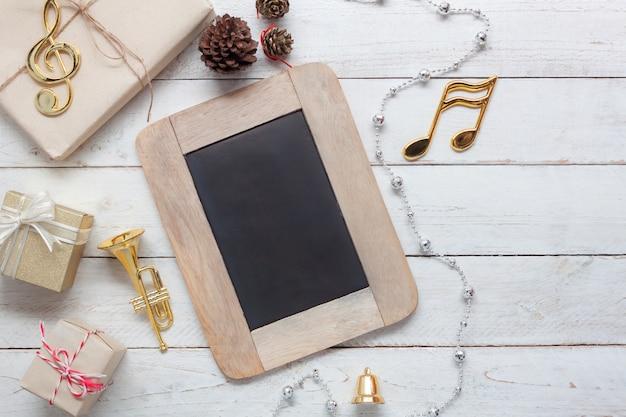 Albero del regalo e della lavagna con gli oggetti per la stagione invernale sull'ufficio di legno bianco d'annata a casa.