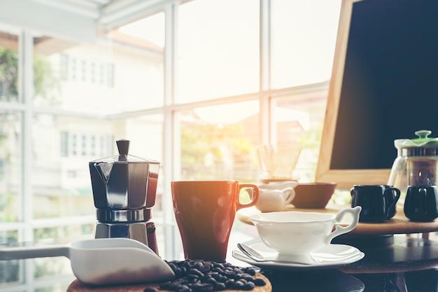 Menu della lavagna sul piano d'appoggio di legno di marrone scuro con la tazza di caffè alla caffetteria della finestra