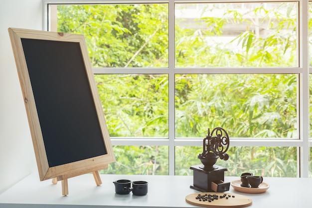 Menu della lavagna sul piano d'appoggio di legno di colore marrone scuro con la tazza di caffè