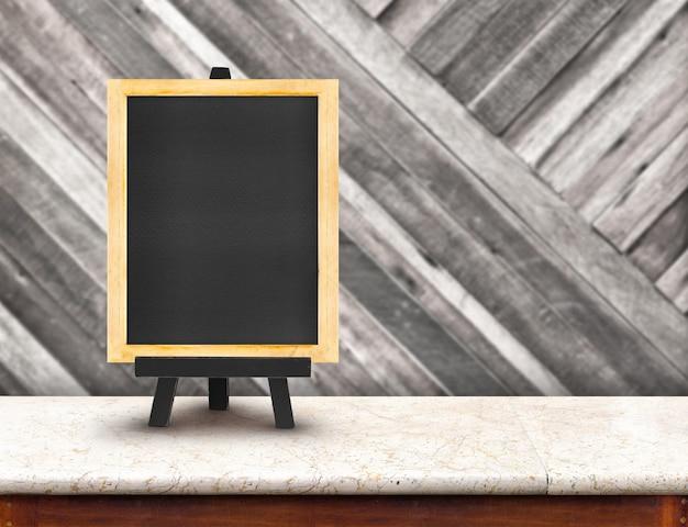 Menu di lavagna con cavalletto sul tavolo di marmo con parete in legno sfocatura
