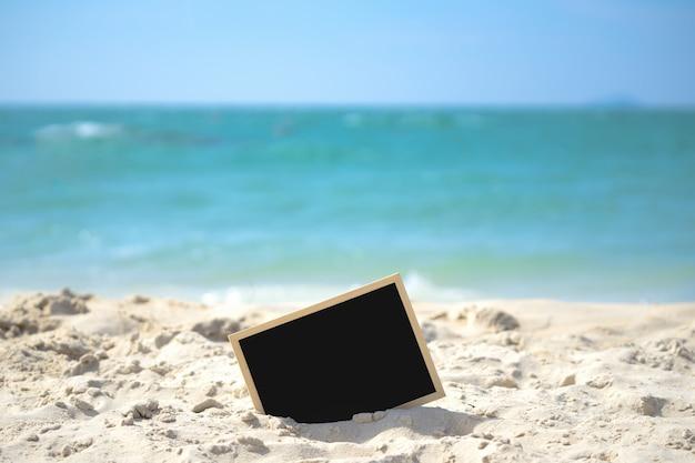 Menu di lavagna con cavalletto sul tavolo di legno in mare, copia spazio per aggiungere il tuo contenuto.