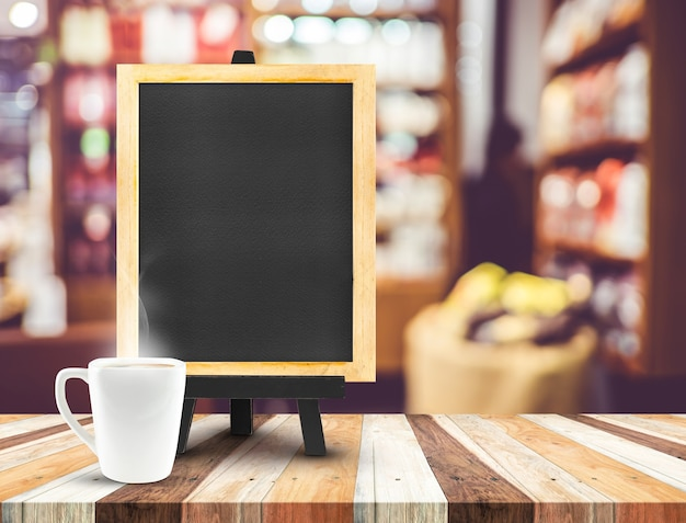 Menu della lavagna con il cavalletto sulla tavola di legno con la tazza di caffè al fondo del caffè della sfuocatura