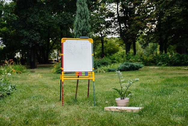 Lavagna nel parco per insegnare ai bambini delle scuole durante la pandemia all'aperto. ritorno a scuola, apprendimento durante la pandemia.