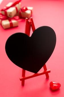 Lavagna a forma di cuore, su sfondo rosso. spazio vuoto per il testo.