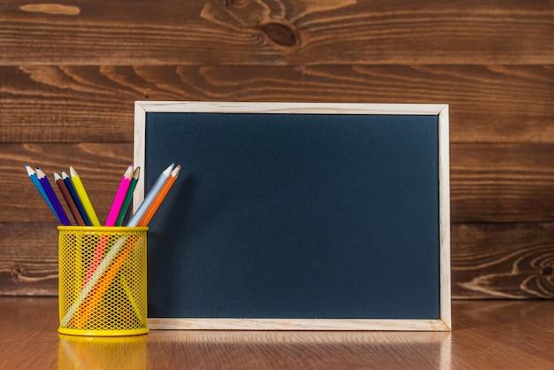 Una lavagna con spazio per il testo, un set di matite colorate con un bicchiere su un legno