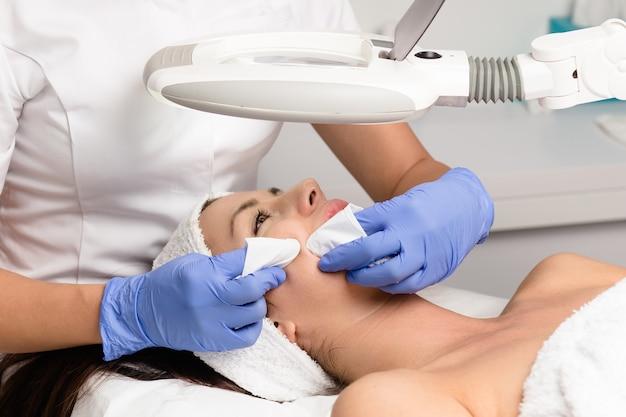 Pulizia dei punti neri sul viso della donna durante il trattamento del viso presso una clinica di bellezza di lusso.