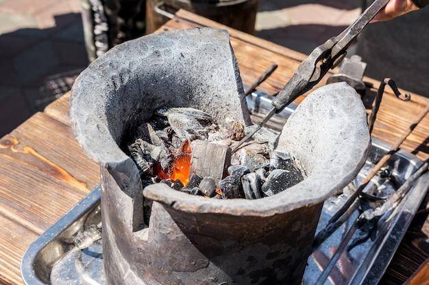 Il fabbro tiene un pezzo di metallo con le pinze e lo riscalda nella fucina una fornace con carbone ardente