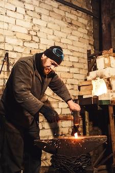 Il fabbro forgiando manualmente il metallo rovente sull'incudine e le scintille volanti