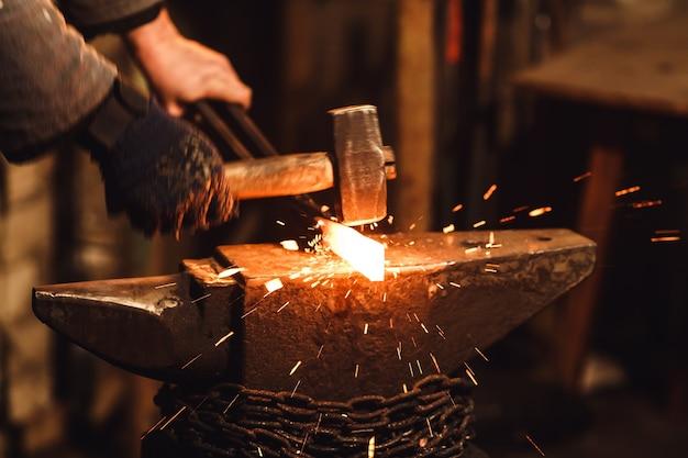 Il fabbro forgiando manualmente il metallo rovente sull'incudine nella fucina con fuochi d'artificio a scintilla.