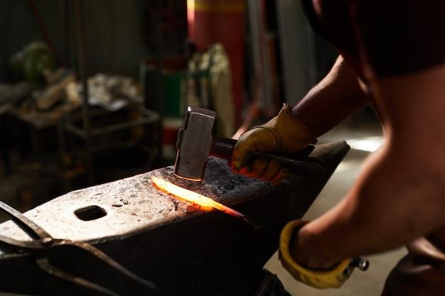Fabbro che modella barra di metallo riscaldata
