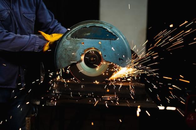 Operaio del fabbro in forgiatura che fa dettaglio con sega circolare