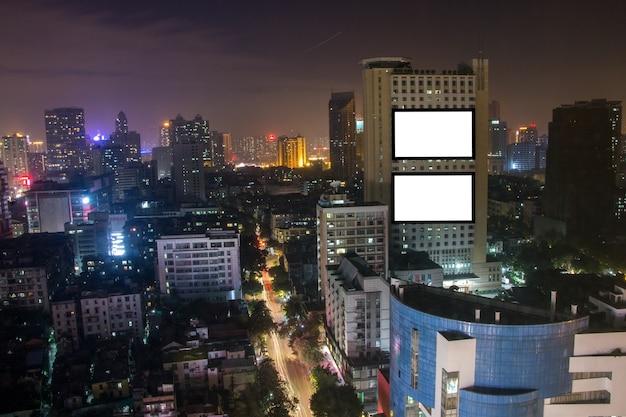 Tabellone per le affissioni di pubblicità in bianco sull'alta costruzione, paesaggio della città, messaggio di testo per commerciale