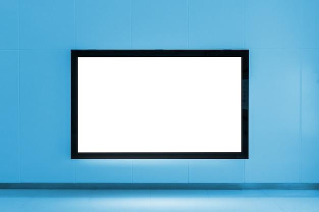 Tabellone per le affissioni di pubblicità in bianco sulla parete alla stazione di metropolitana sul tono di colore blu