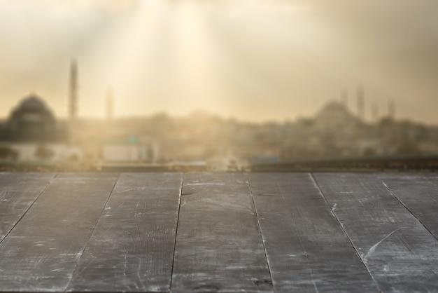 Tavolo in legno grigio scuro strutturato invecchiato vuoto su uno sfondo sfocato del vecchio paesaggio urbano durante la giornata di sole per esporre e montare i tuoi prodotti.