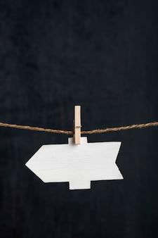 Puntatore a freccia vuoto appeso con mollette sulla corda sulla superficie nera. targhetta piccola. copia spazio. cornice verticale.