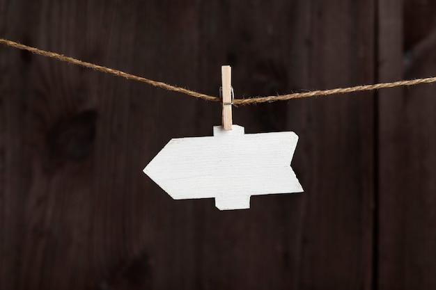 Puntatore a freccia vuoto appeso con mollette su corda, superficie in legno. targhetta piccola. copia spazio.