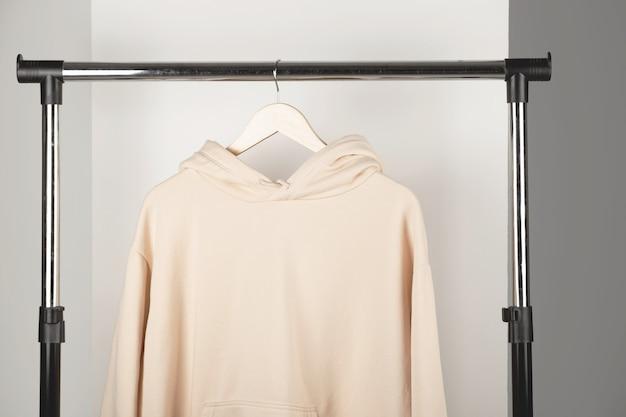 Mockup di felpa unisex beige bianco su felpa con cappuccio appendiabiti mock up in interni minimi