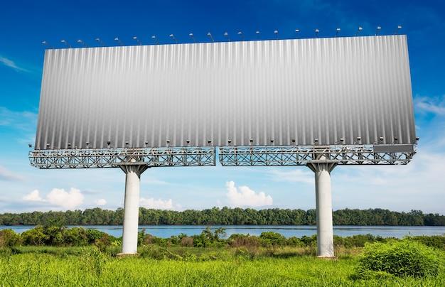 Tabellone per le affissioni in bianco per la pubblicità sulla riva del fiume e sul cielo blu