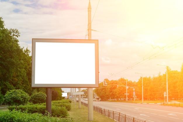 Tabellone vuoto accanto all'autostrada, lo sfondo per la tua pubblicità. modello.
