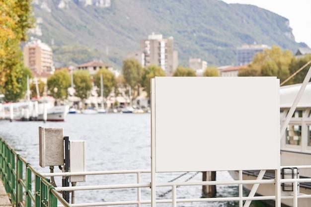 Modello vuoto del tabellone per le affissioni per la pubblicità del fondo dell'argine del lago banner mock up vicino al lago